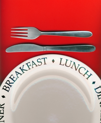 Knife and fork with white plate on red background