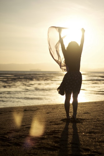 Woman standing on beach with arms in the air in celebration.