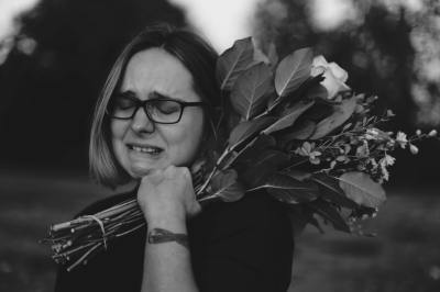 Woman holding a bunch of flowers and crying.