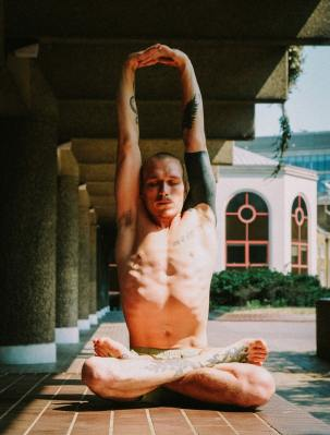 Bare-chested man with tattoos in yoga pose.