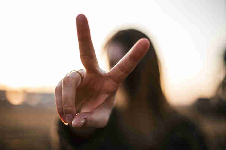Woman doing the peace sign with her fingers.